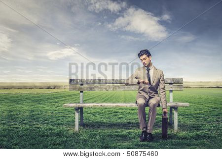businessman waiting sitting on a park bench in countryside