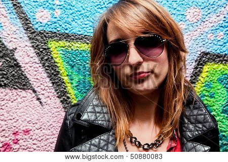 Stylish fashionable girl posing against colorful graffiti wall. Fashion, trends, subculture
