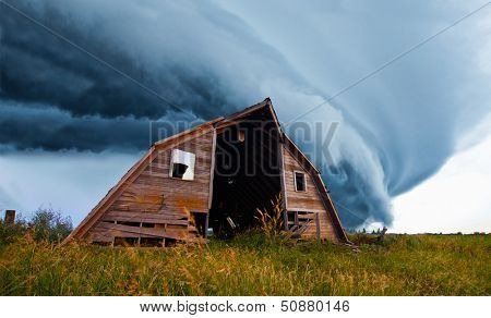 tornado forming behind old barn on american plains