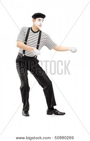 Full length portrait of a male mime artist performing pulling virtual rope isolated on white background