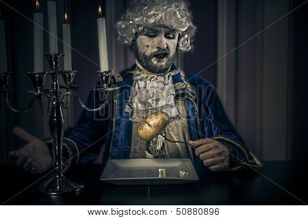 Modern prince, eating potatoes. Young in eighteenth century image posing with candle