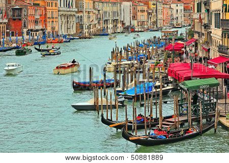 VENICE - NOVEMBER 13: Grand Canal, gondolas and promenade with bars and restaurants - one of the most popular places with tourists as seen from Rialto Bridge in Venice, Italy on November 13, 2012.