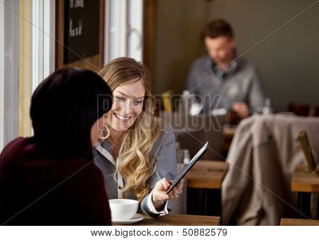 Two women sitting in rustic cafe looking at pictures on digital tablet