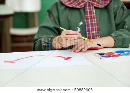 Midsection of little boy painting at desk in preschool