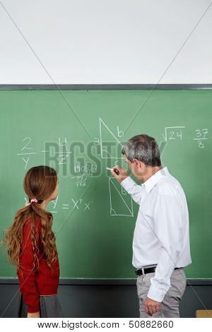 Side view of male teacher teaching mathematics to teenage schoolgirl in classroom