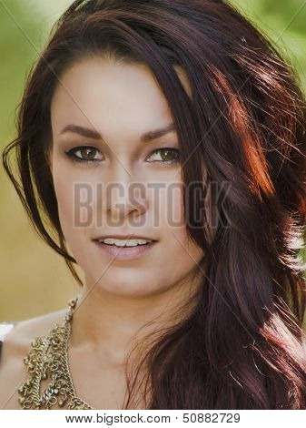 Beautiful young woman's face with fresh clear skin and red wavy hair.