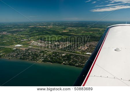 An Airplane Wing High Over Aerial View Lake And Small Town
