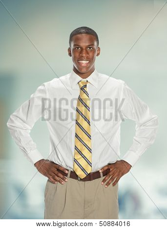 Young African American businessman with hands akimbo inside office building