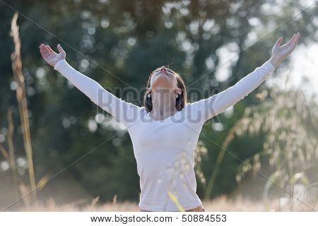 Young woman enjoying nature, arms raised