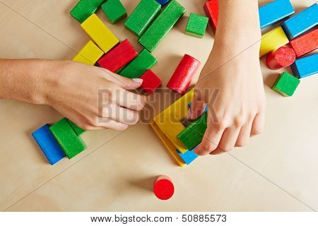 Two female hands playing with colorful wooden building blocks