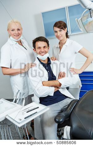 Dentist with group of dental assistants in his dental practice