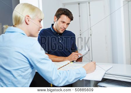 Man with appointment book scheduling an appointment at reception of dentist