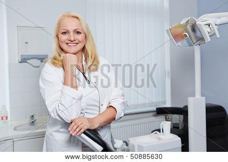 Portrait of a smiling elderly female dentist in her dental practice
