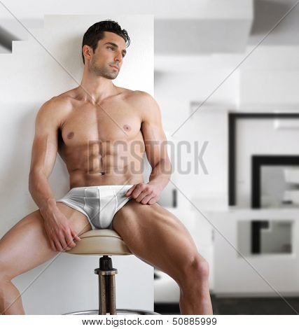 Very sexy young fit man in white underwear in modern contemporary interior setting