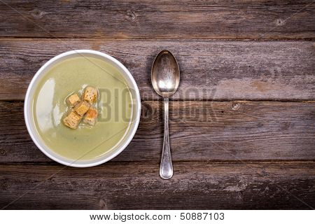 A bowl of leek and potato soup with bread croutons, over old wood table with fresh leeks and potatoes alongside