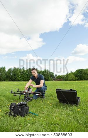Portrait of young technician assembling UAV helicopter in park against cloudy sky