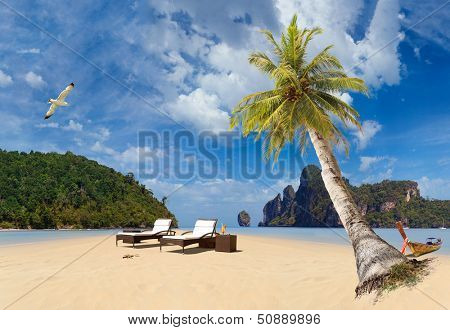 Tropical beach of Ko Phi Phi Don island with sunbeds and long tailed boat