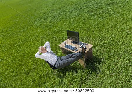 Business aerial high angle concept shot showing an older male man or businessman relaxing feet up at a desk with a computer in a green field