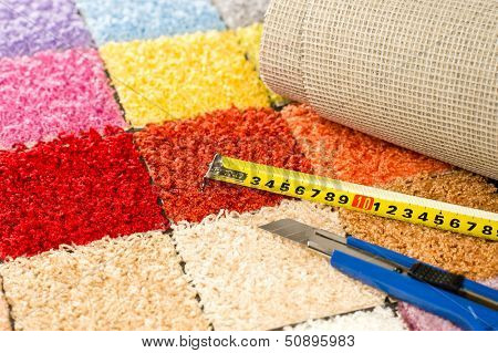 Carpeting colorful swatches, boxcutter and tape measure