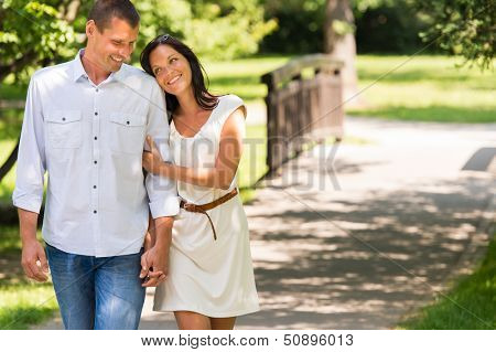 Smiling couple walking in a park hand in hand