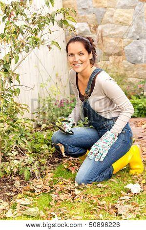 Smiling woman gardening yard fall hobby housework kneeling dry leaves