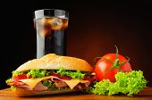 stock photo of deli  - still life with deli sub sandwich fresh vegetables and cola soft drink - JPG