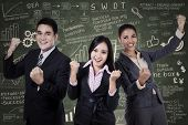stock photo of filipino  - Successful business team celebrating their triumph with arms up - JPG