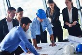 stock photo of engineer  - business people group on meeting and presentation  in bright modern office with construction engineer architect and worker looking building model and blueprint planbleprint plans - JPG