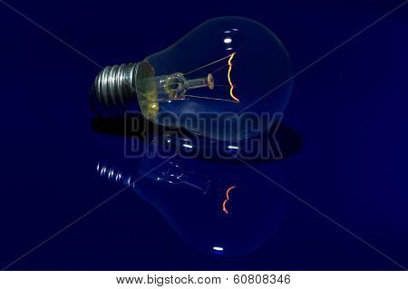 Light Bulb With Burning Filament Lay On Blue Surface With Reflection