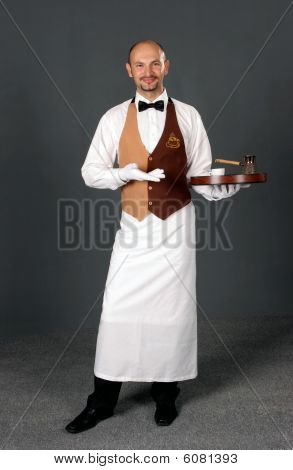 Waiter In Uniform With Percolator And Cup Of Coffe