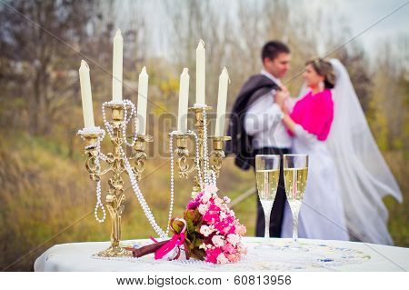 Bride And Groom Posing At The Decorated Banquet Table In Park In Summer