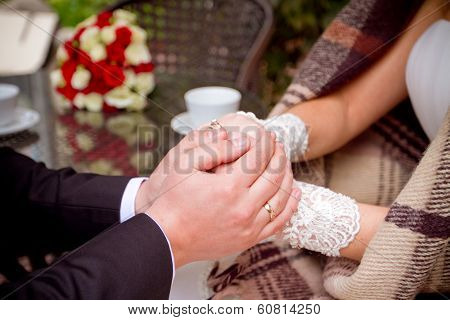Couple Holding Hands At Wooden Table