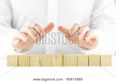 Protective Hands Above A Line Of Nine Blank Wooden Cubes