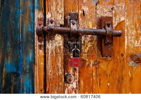 Padlocked Rusty Bolt on Old Wood Door