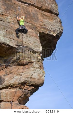 Young Woman Climbing A Rock