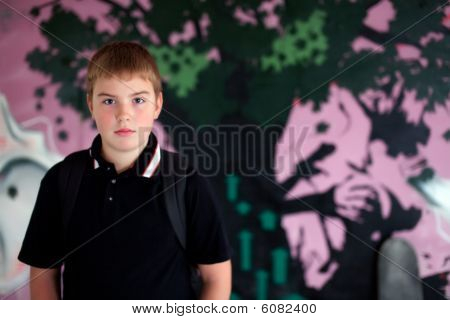 Rapaz com saco de ombro roxo Agaisnt Graffity parede