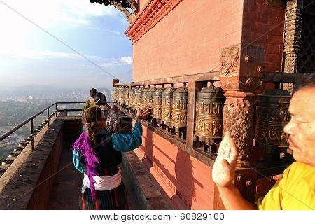 Buddhist Pilgrims Circling Around The Swayambhunath Temple And Spinning The Prayer Wheels