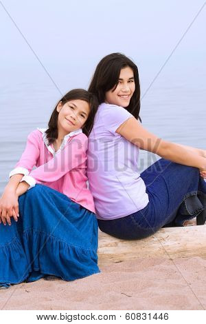 Two Sisters Sitting By Beach