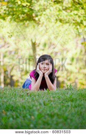 Little Girl Lying Down On Grass