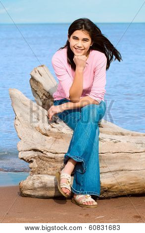 Beautiful Biracial Teen Girl Sitting On Fallen Log By Lake Shore In Summer