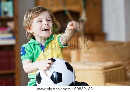 Little Blond Preschool Boy Of 4 Years With Football Looking Soccer World Cup On Tv.