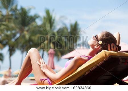 Happy young woman in bikini enjoying her time on chaise-longue luxury pool side