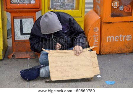 homeless man sleeping beside newpaper boxes