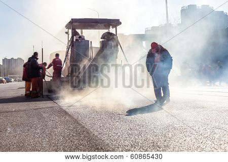 Workers making asphalt with shovels at road construction