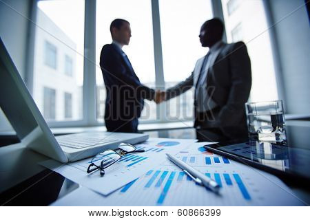 Image of eyeglasses, glass of water, pen, laptop, touchpad and financial documents at workplace with businessmen handshaking on background