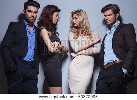 portrait of two jealous women looking at eachother beside their men who are holding their hands in their pockets. on a gray background
