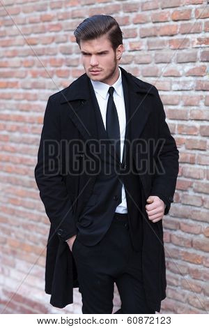 young business man posing outdoor with a hand in his pocket and the other on his overcoat while looking to his side, away from the camera