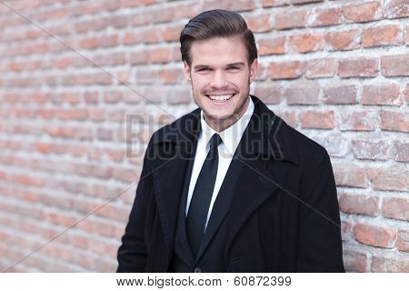 portrait of an elegant young business man posing outdoor, in front of a brick wall and laughing into the camera