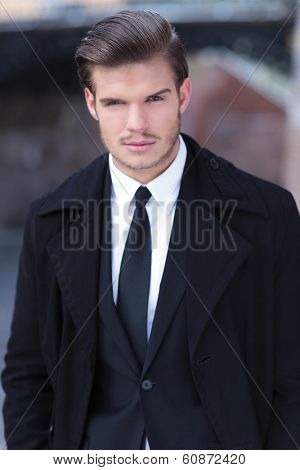 outdoor photo of an elegant young business man looking into the camera with his eyebrow raised