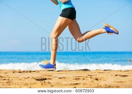 Sporty blonde woman in sportswear jogging on a sunny beach